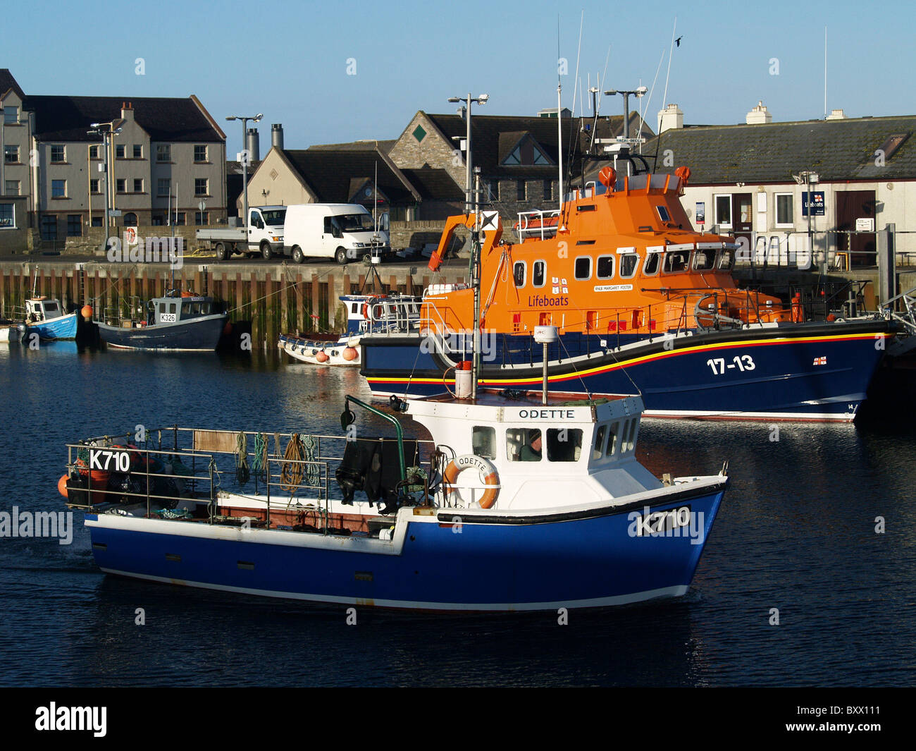A small fishing boat passes the Kirkwall Lifeboat, in the Orkney Islands, Scotland - Stock Image