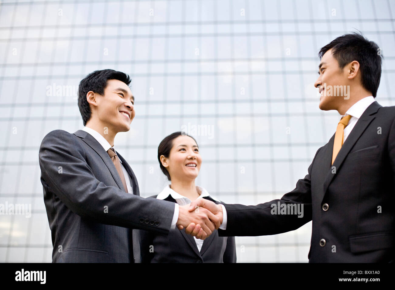 Businessmen shaking hands in front of a tall building - Stock Image