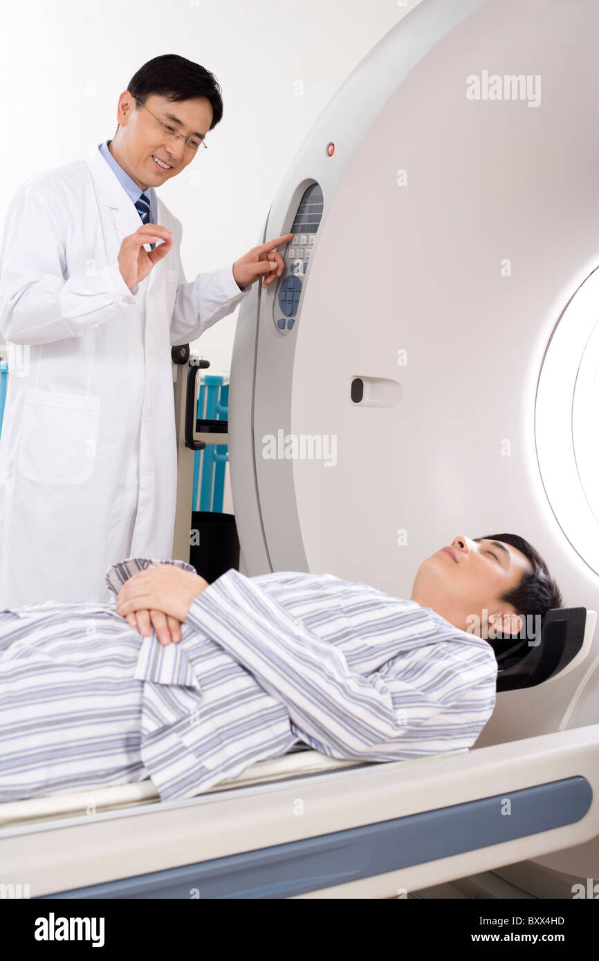 Medical professional helping a patient into a MRI scanner - Stock Image