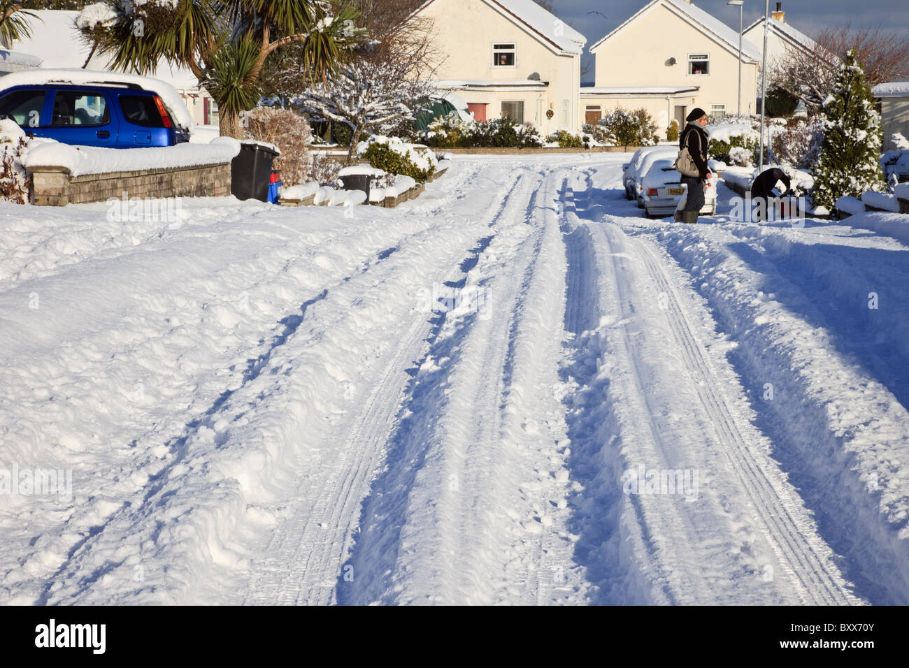 Deep ruts from tyre tracks in snow on suburban street after heavy winter snowfall in 2010. Wales UK Britain - Stock Image