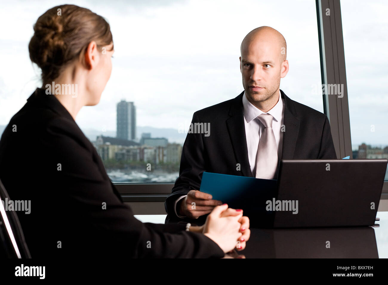 Young woman having a job interview, skeptical boss - Stock Image