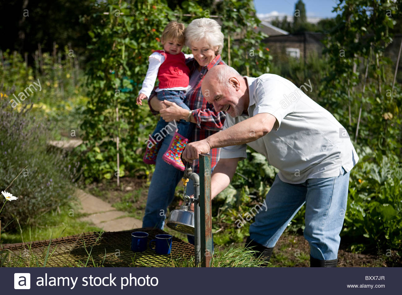 A family filling a kettle on an allotment - Stock Image