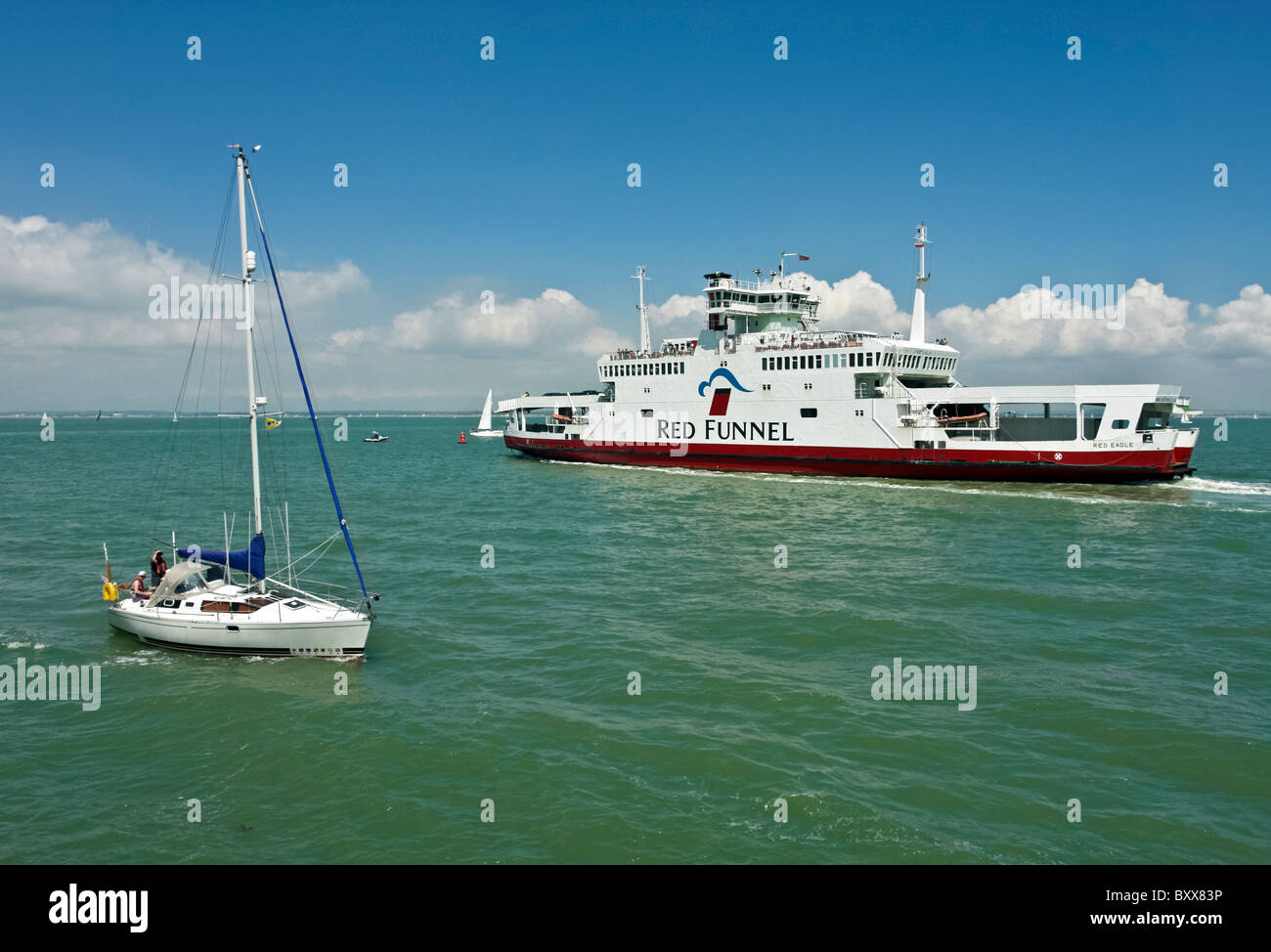 A sailing boat passes Red Funnel ferry Red Eagle in the Solent off Cowes in the Isle of Wight England - Stock Image