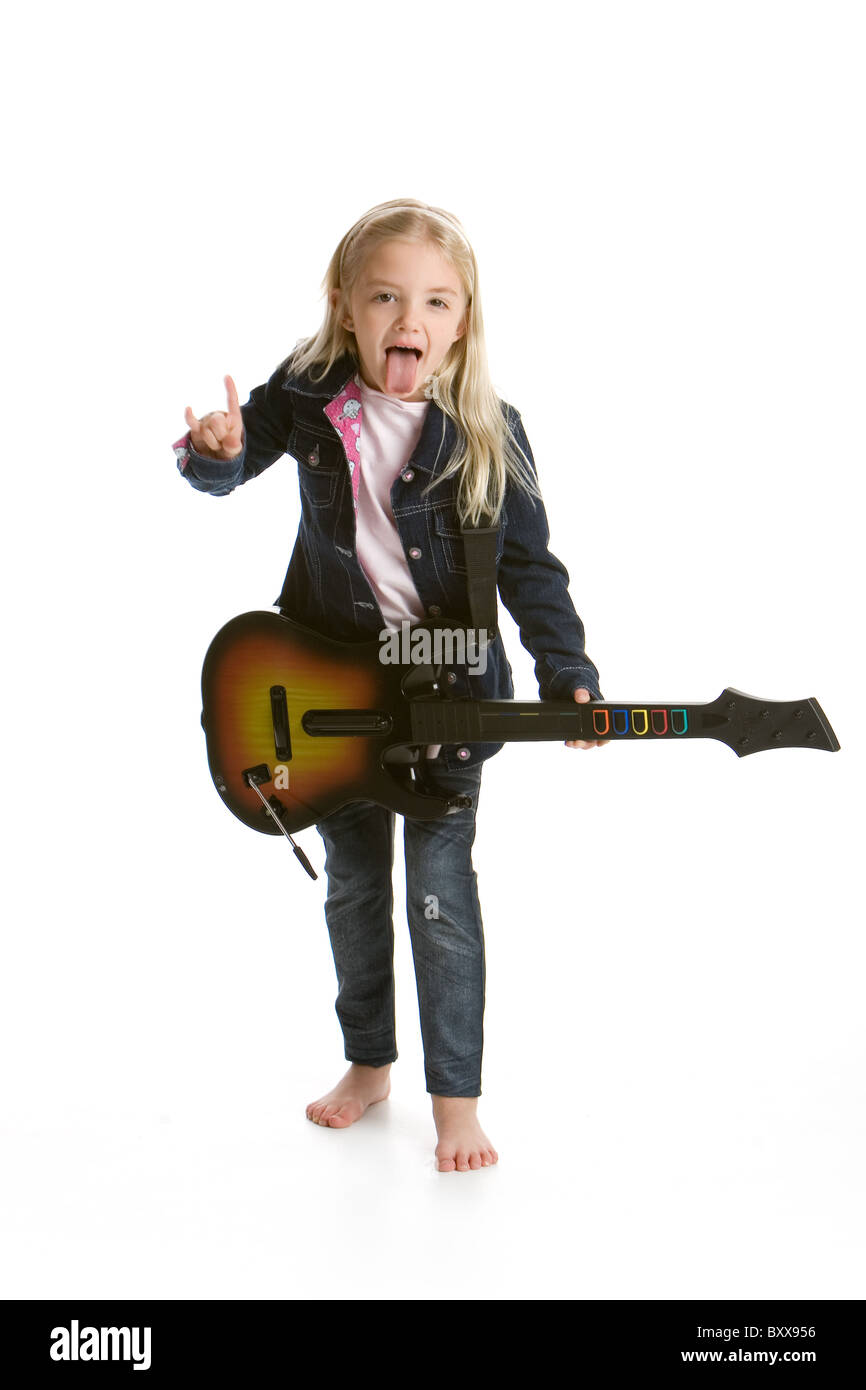 Cute little girl playing video game guitar and rocking out - Stock Image