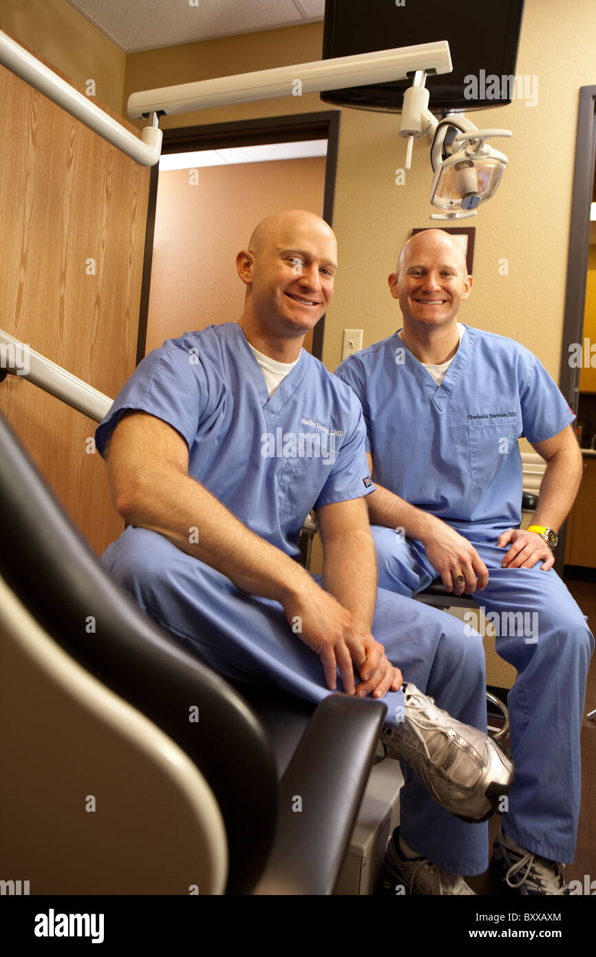 Dentists who are identical twins pose in an examining room in the clinic where they practice together in Austin, - Stock Image