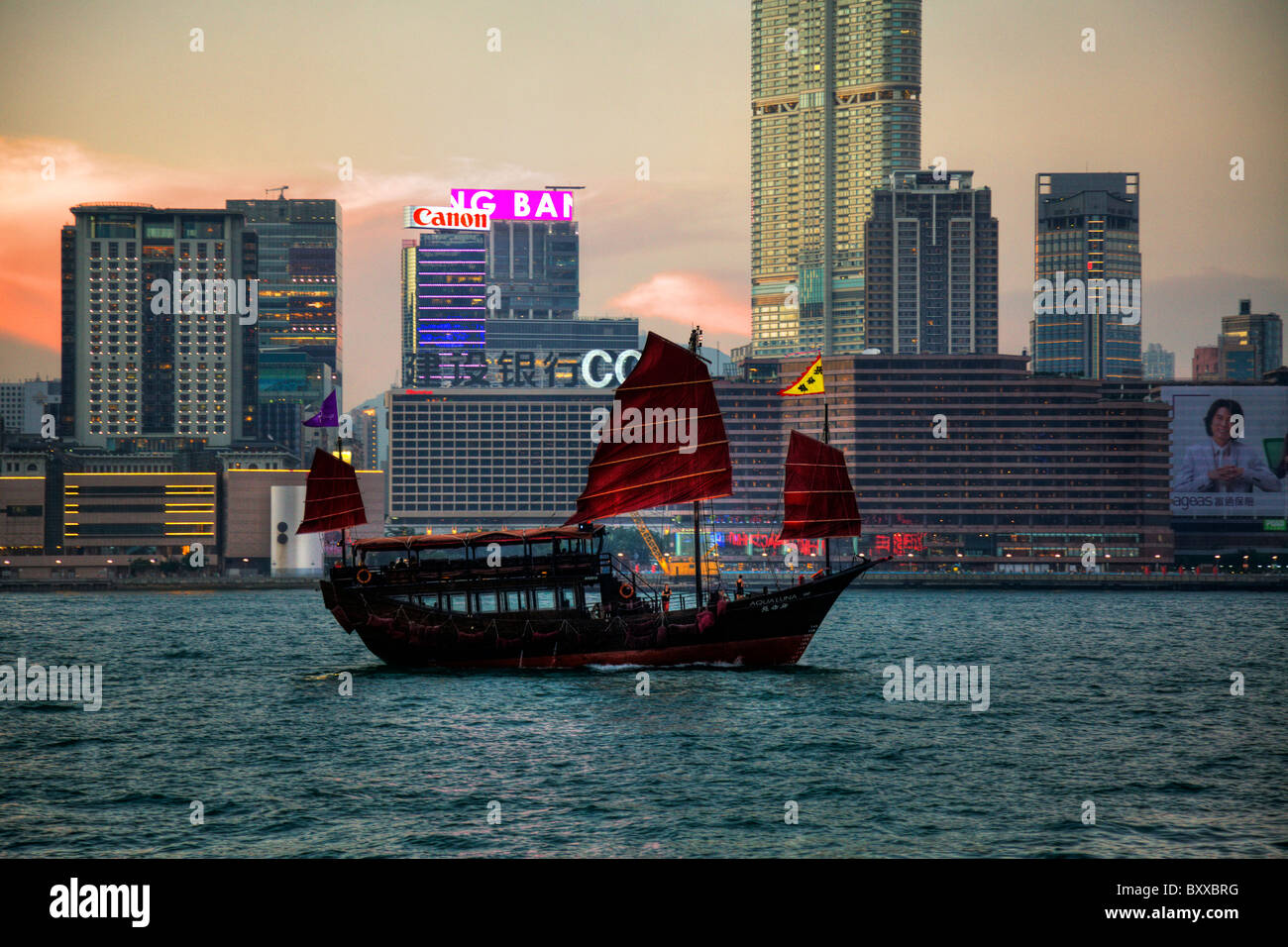 The Kowloon skyline at dusk showing the iconic red sail junk from Hong Kong Island - Stock Image