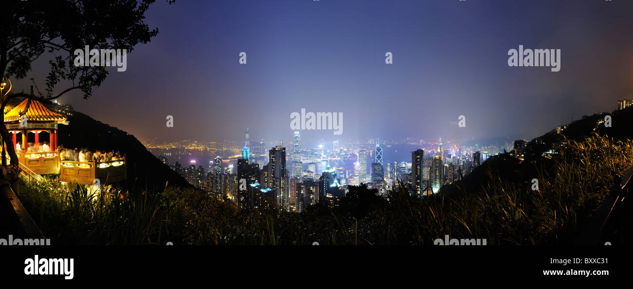 Hong Kong panorama across Victoria Harbour towards Kowloon from Victoria Peak, at night with the city lit up. - Stock Image
