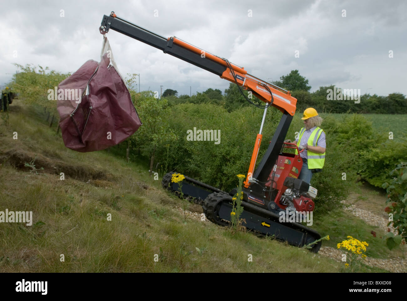 A Hinowa Mammut Verde caterpillar with hoist is put through its paces clearing fly tipped rubbish UK - Stock Image