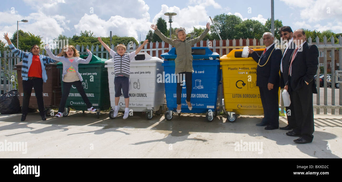 Children jump at the opening of a recycling centre waste materials UK - Stock Image