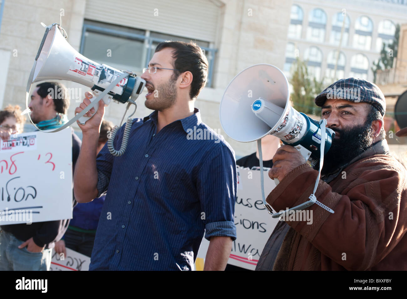 Israeli and Palestinian activists stand side by side during a weekly protest against Jewish settlements in East Stock Photo