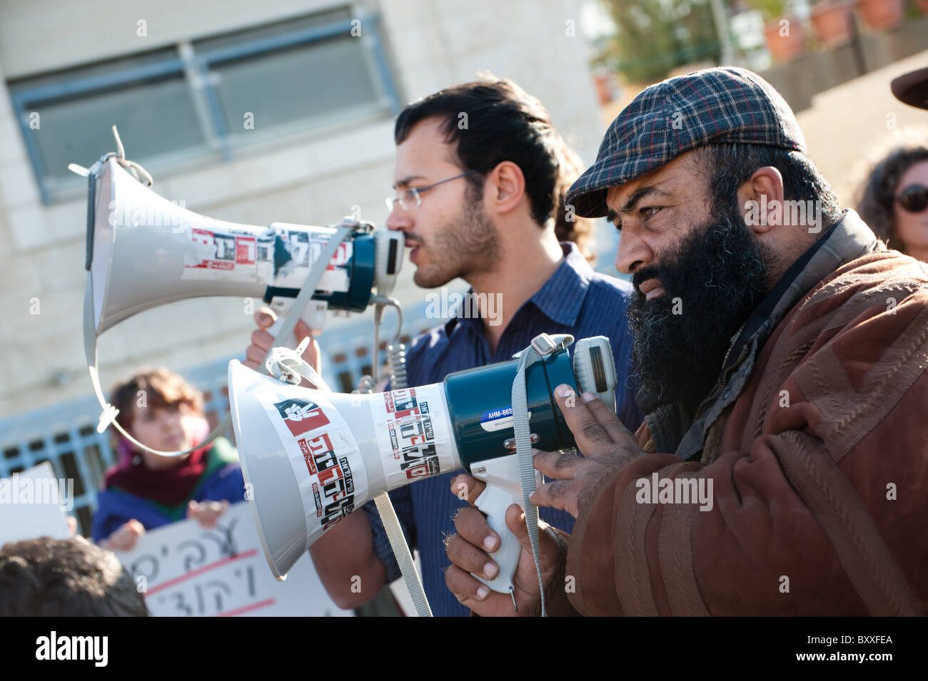 Israeli and Palestinian activists stand side by side during a weekly protest against Jewish settlements in East - Stock Image