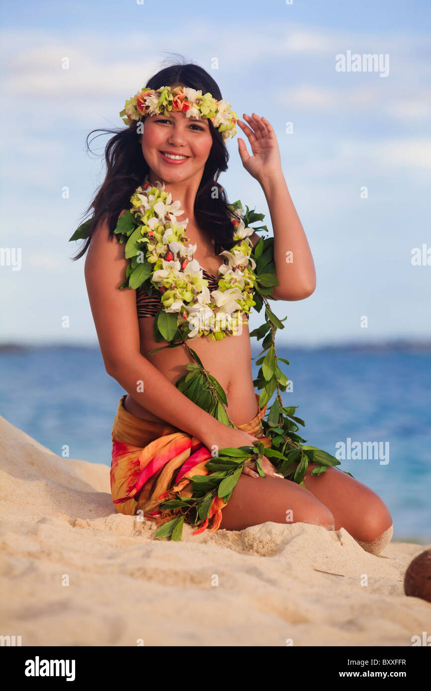 hula dancer sitting on the beach - Stock Image