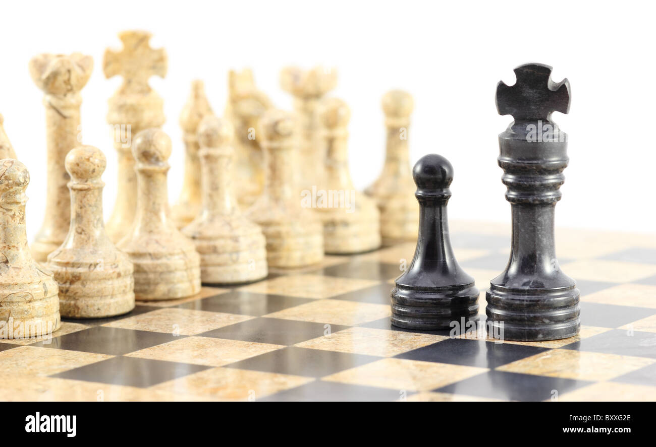 Loyalty to the King - A pawn and his king face off against the entire army of opposing chess pieces. - Stock Image