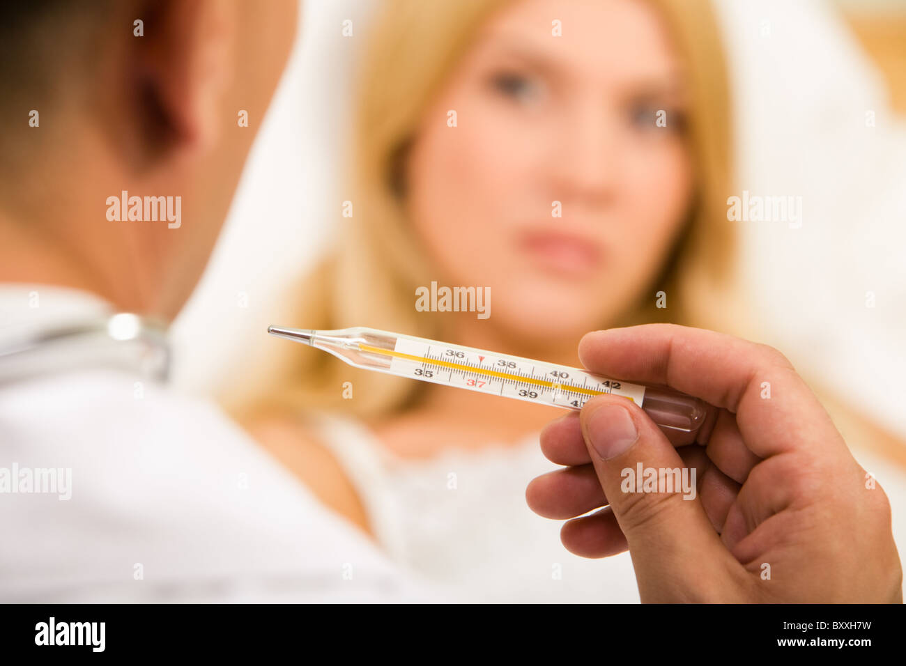 Close-up of doctor's hand holding thermometer with sick woman on background - Stock Image