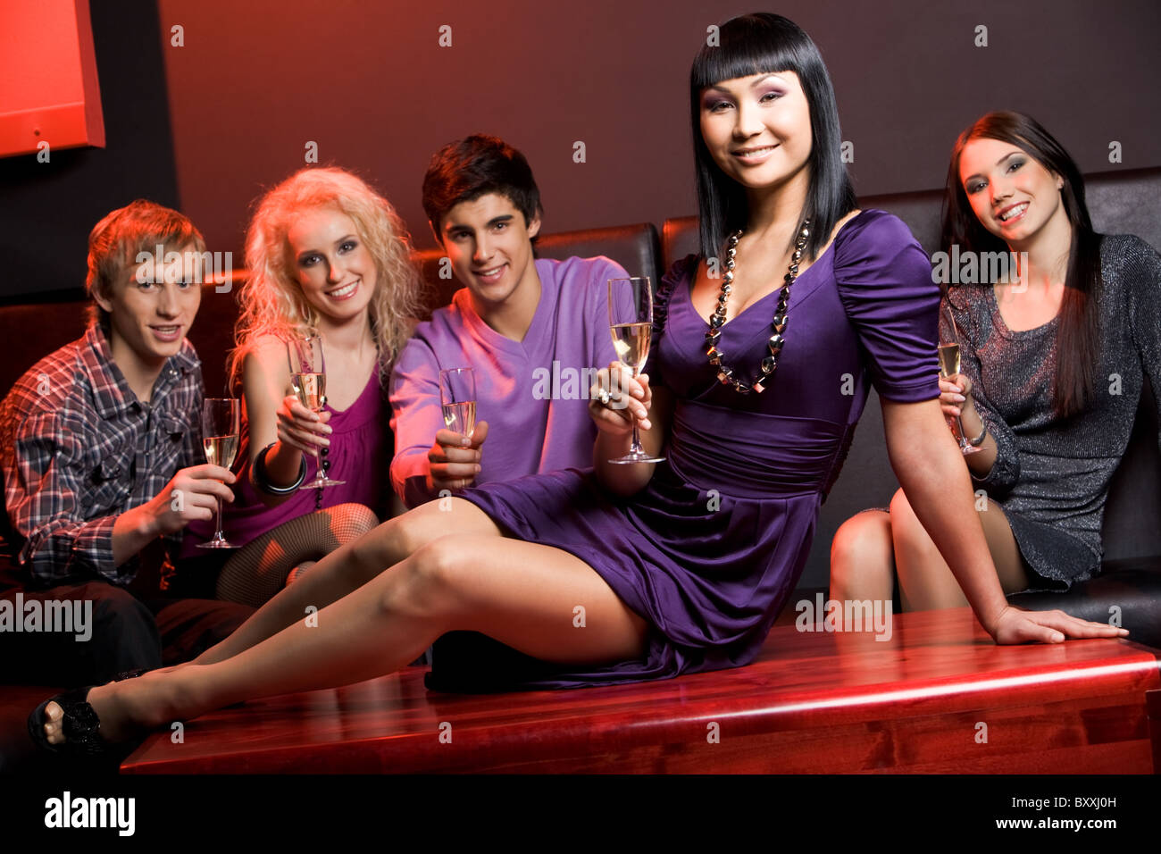 Image of glamorous woman with champagne sitting on table on background of her friends - Stock Image