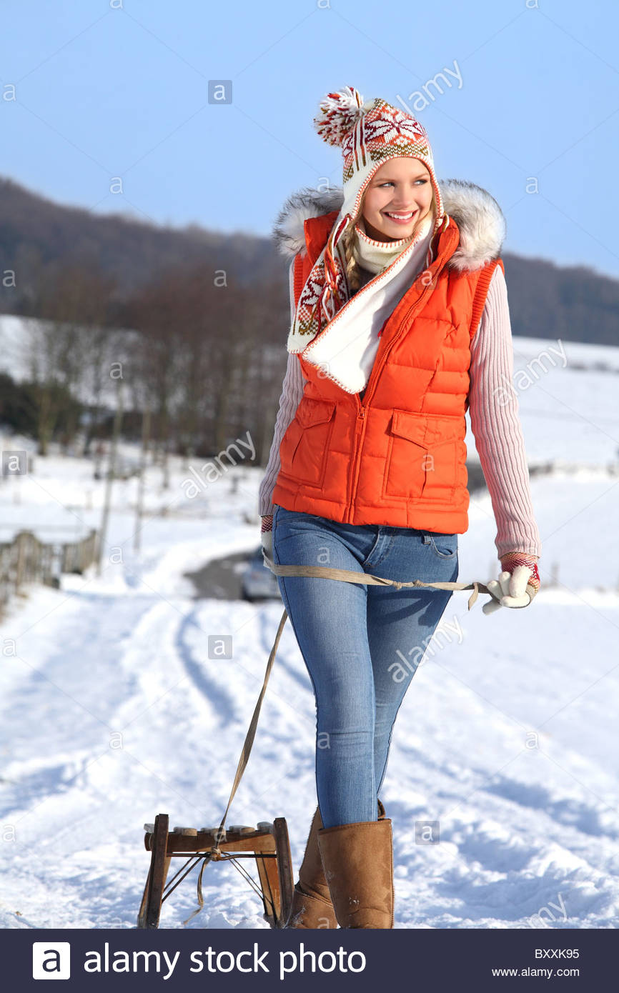 young woman enjoying a walk in winter landscape with her sledge - Stock Image