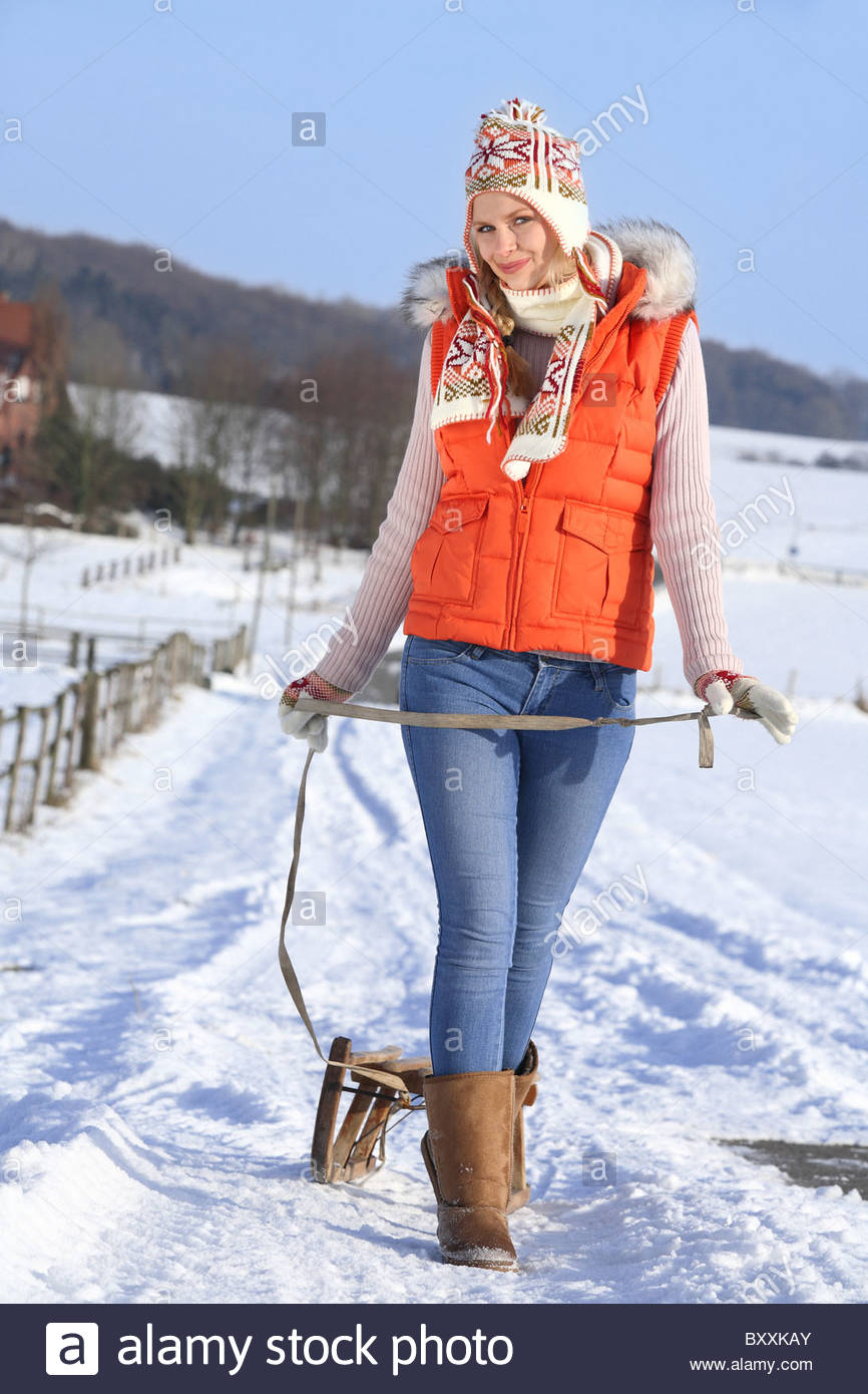 young woman enjoying a walk in winter landscape with her sledge Stock Photo