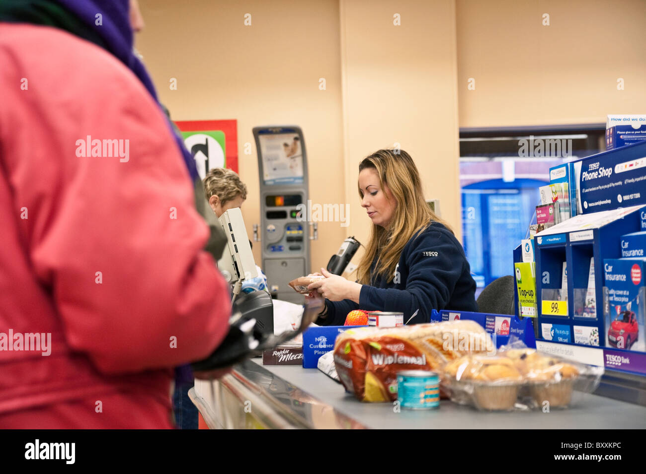 Check out operator in a Tesco supermarket, UK. Checkout cash till inside a store. Food items on conveyor belt at - Stock Image