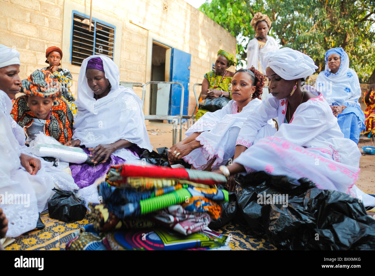In Ouagadougou, Burkina Faso, women bring gifts of clothing to a child's baptism. - Stock Image