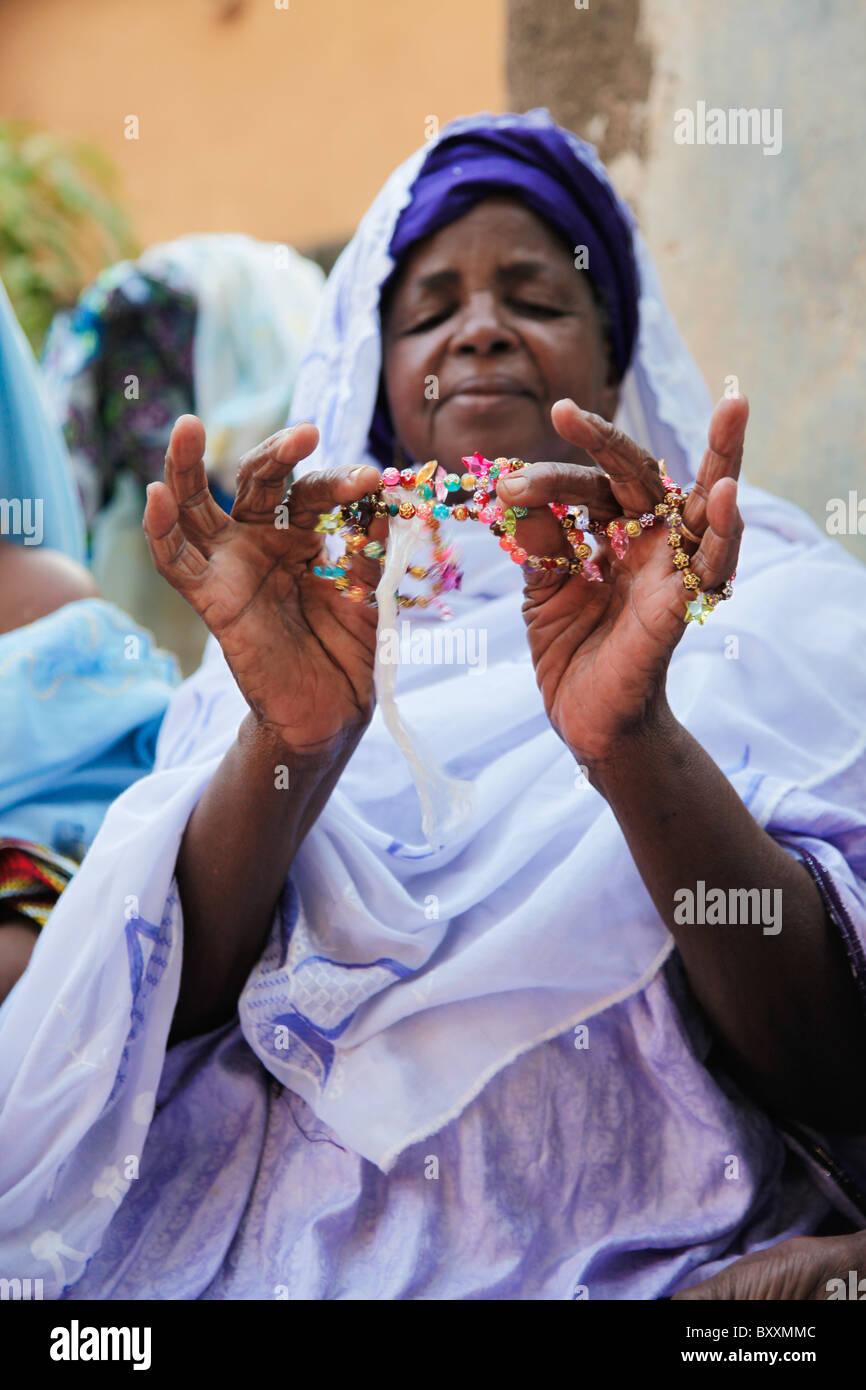 A woman shows friends a bead necklace during a baptism in Ouagadougou, Burkina Faso. - Stock Image