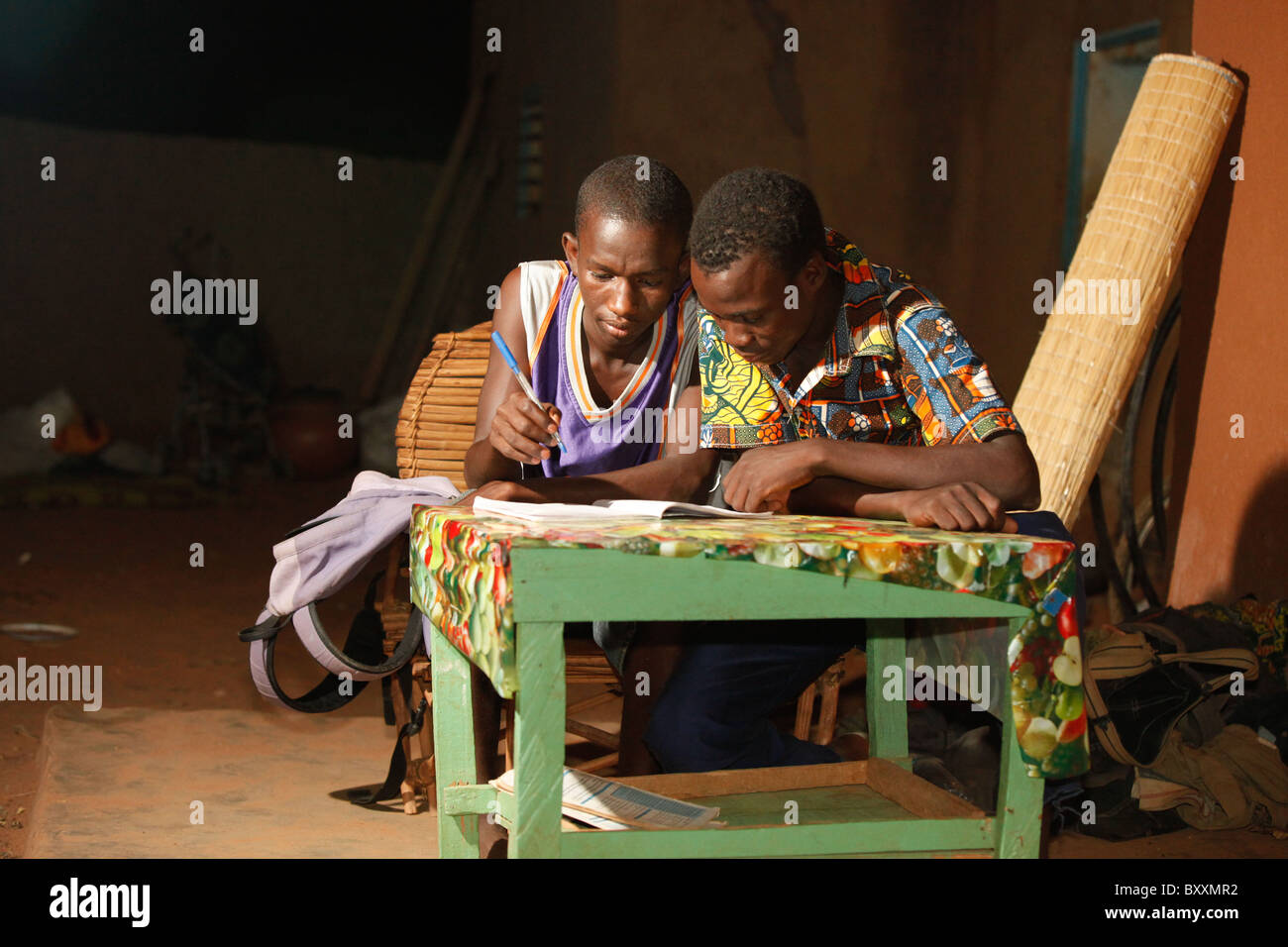 Two junior high school students (equivalent of the 7th grade in the US) study at night in the yard of their home. - Stock Image