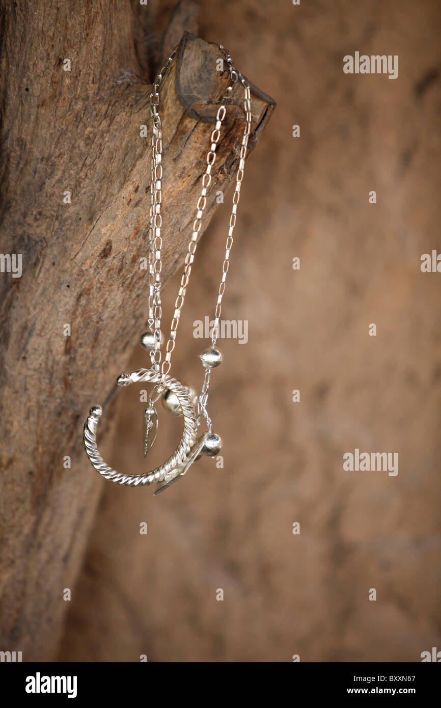 At the blacksmith's in the village of Bourro in northern Burkina Faso, a silver necklace and bracelet hang from - Stock Image