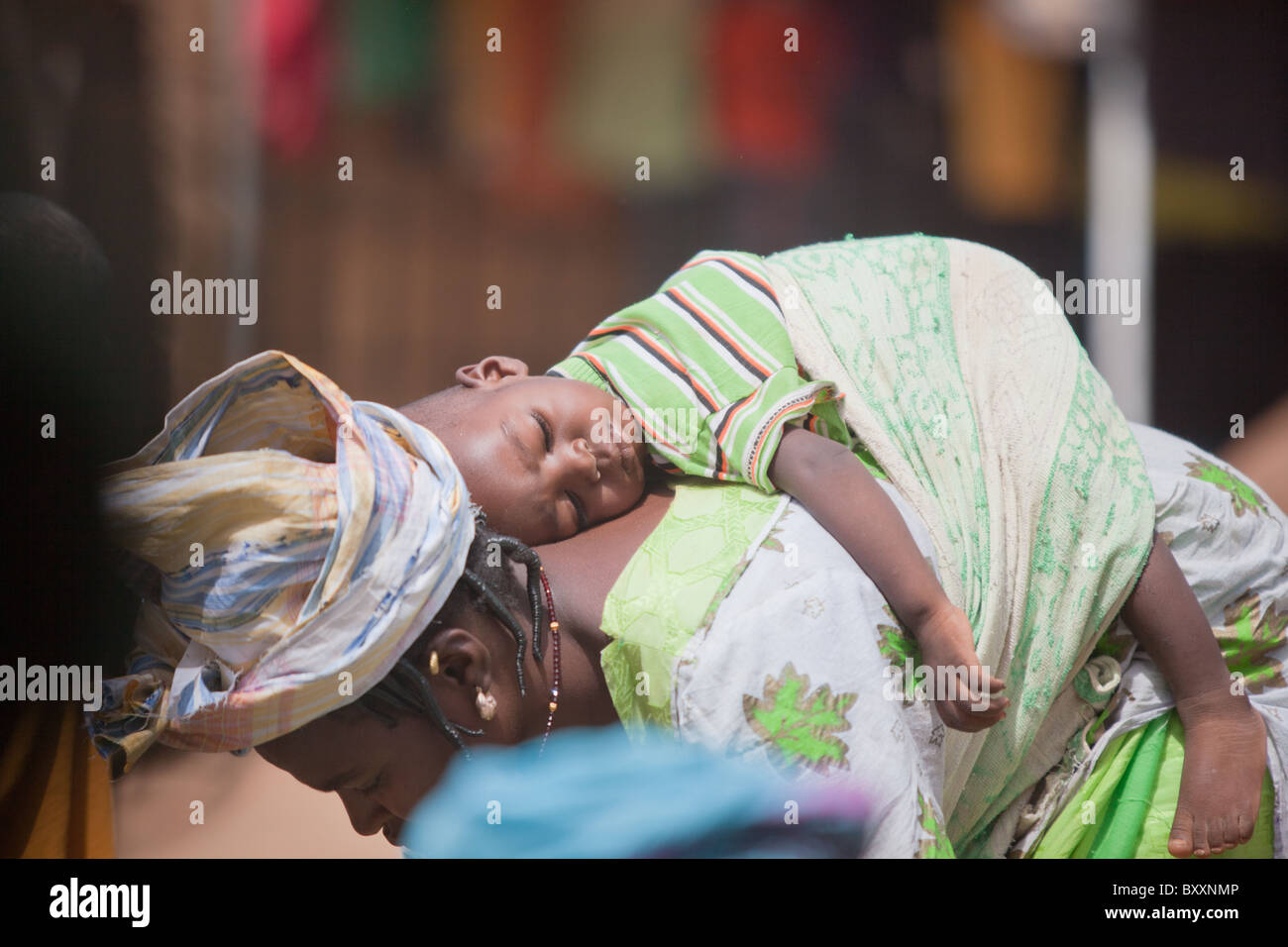 In the town of Djibo in northern Burkina Faso, a woman bends over to examine okra in the market, baby on her back. - Stock Image