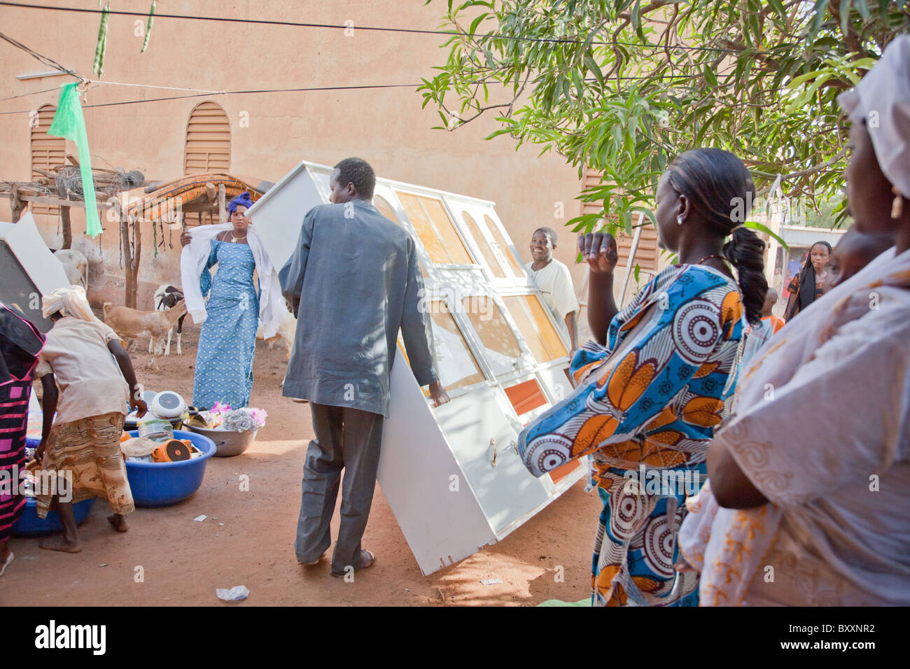 In Burkina Faso, a Fulani wedding has taken place. On the day of the 'bantule,' friends/family move furniture - Stock Image
