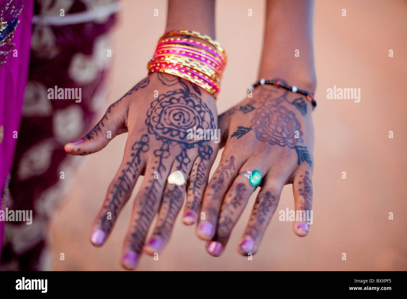 In the days leading up to Tabaski, young women in Djibo, Burkina Faso have their hands decorated with henna. - Stock Image