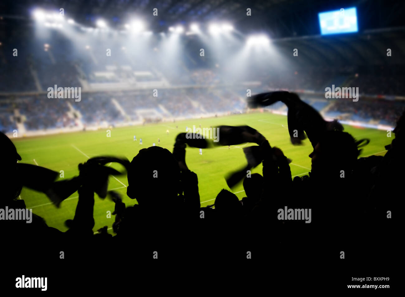 Silhouettes of fans celebrating a goal on football / soccer match - Stock Image