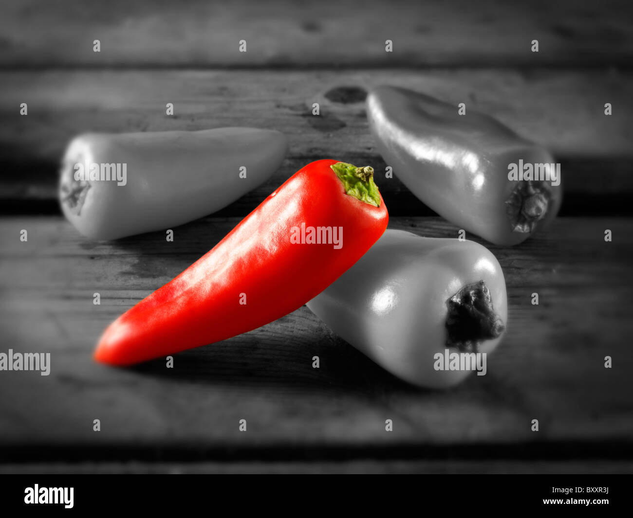 Single red sweet pepper amongst other mixed peppers - Stock Image