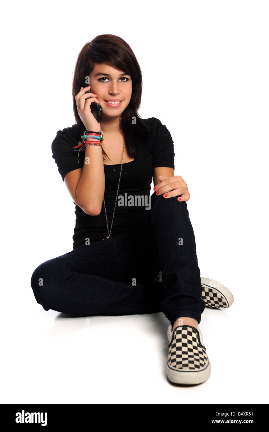 Hispanic teen using cell phone isolated over white background - Stock Image