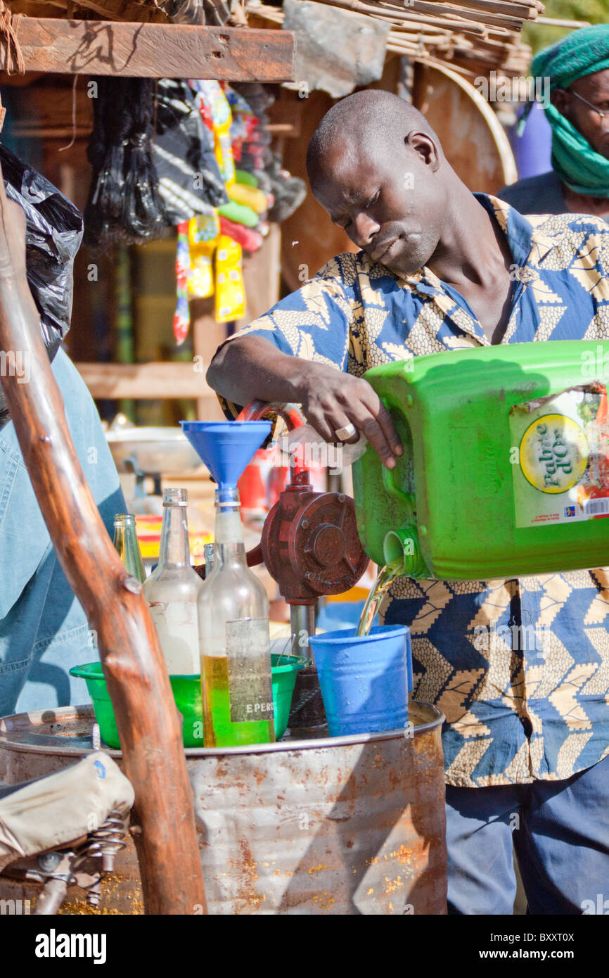 In the town of Djibo in northern Burkina Faso, a man sells peanut oil for cooking in the market. - Stock Image