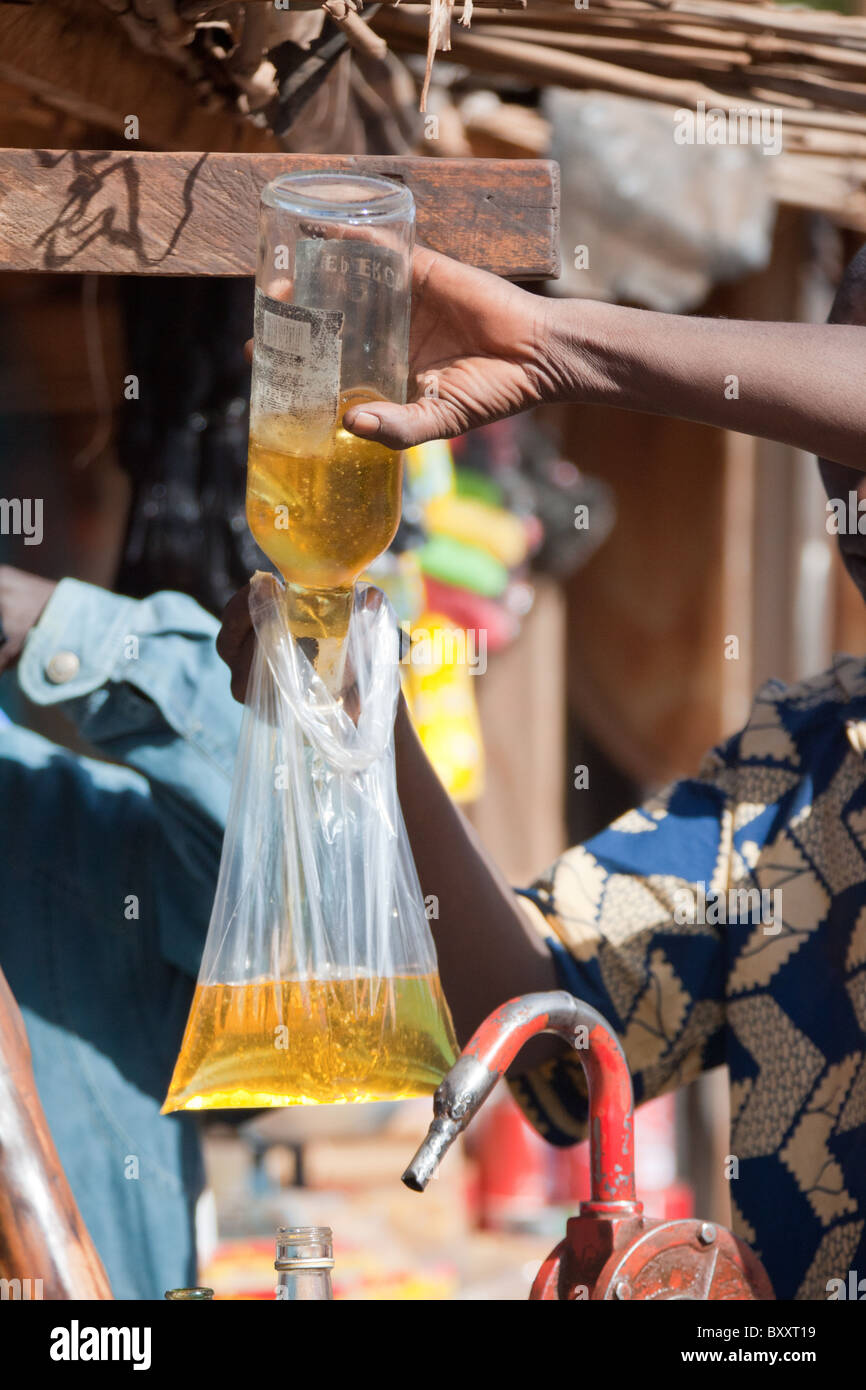 In the town of Djibo in northern Burkina Faso, a man sells peanut oil by the liter. The purchased oil is placed - Stock Image