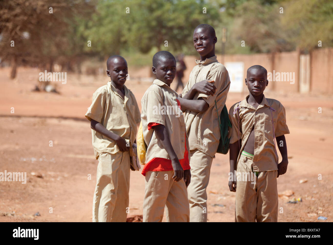 Junior high / high school students in uniform head home through the market in Djibo, northern Burkina Faso. - Stock Image