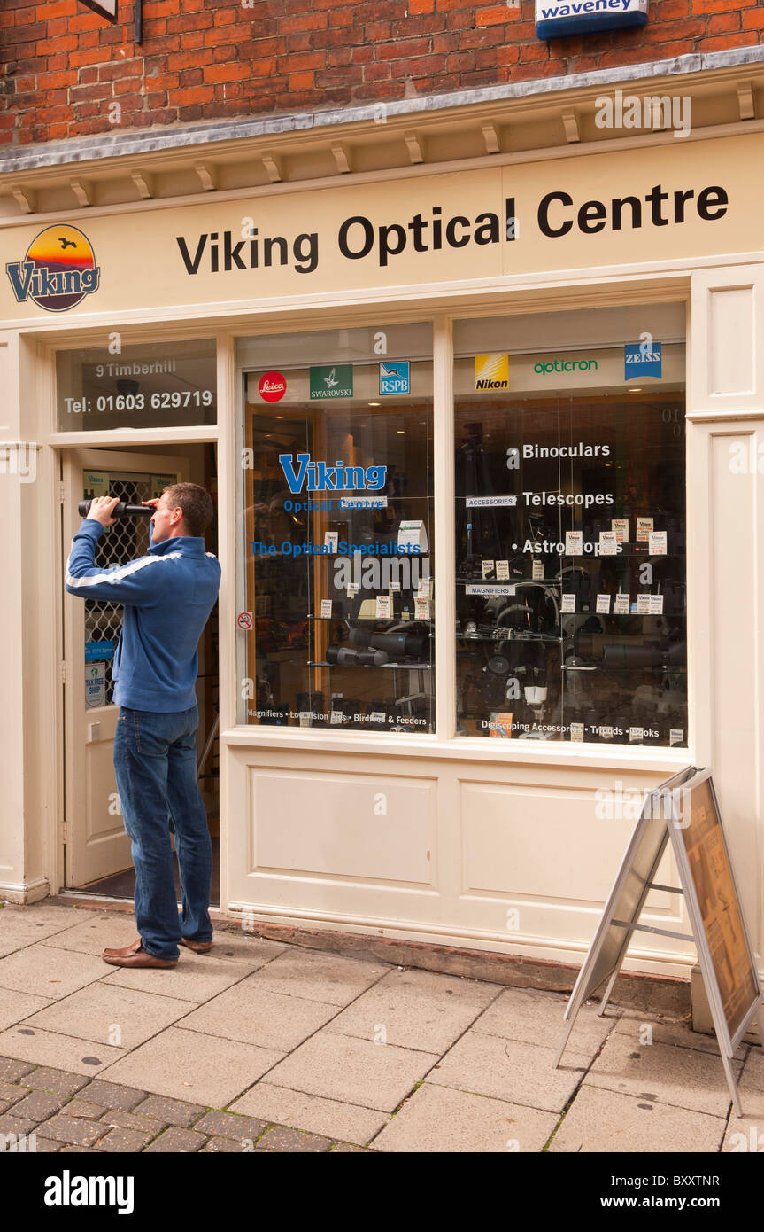 A man testing a spotting scope at Viking optical Centre in Norwich , Norfolk , England , Great Britain , Uk - Stock Image