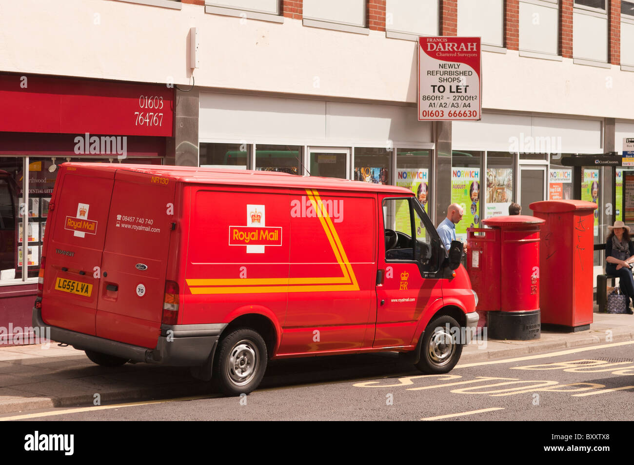 A postman emptying a postbox near his royal mail van in Norwich , Norfolk , England , Great Britain , Uk - Stock Image