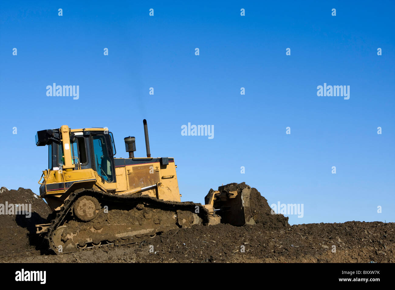 Bulldozer in operation moving dirt and clearing the land. Room for copy above. - Stock Image