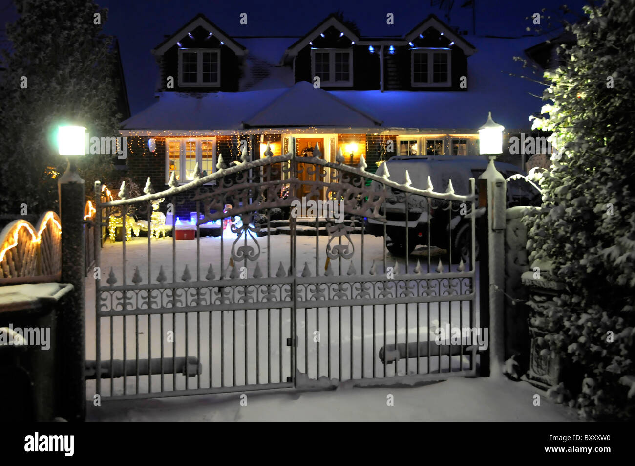 Snow and gated house with Christmas lights - Stock Image