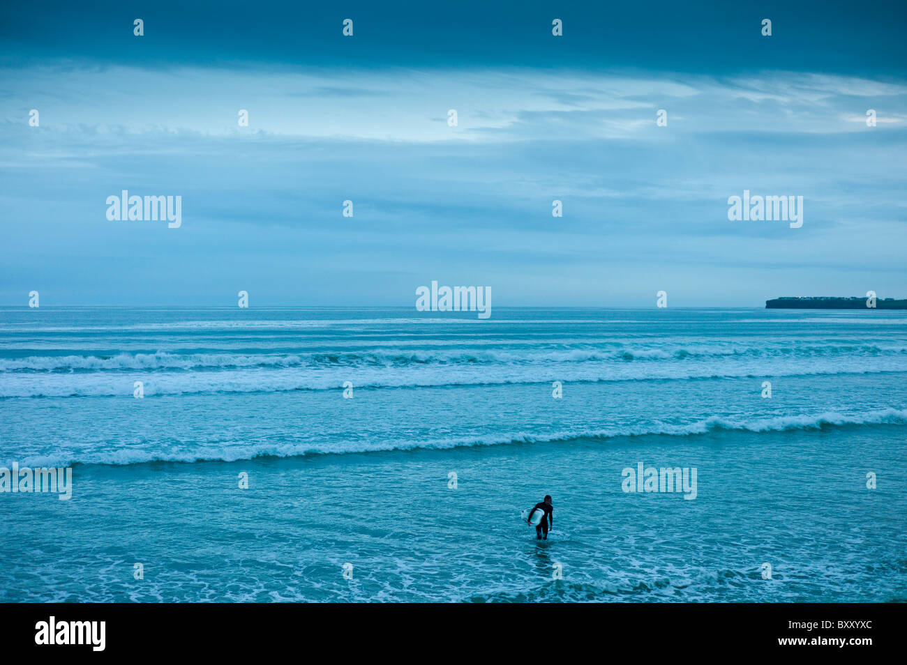 Lone surfer leaving the surf at high tide at beach resort of Lahinch (Lehinch) at twilight, County Clare, West Coast - Stock Image