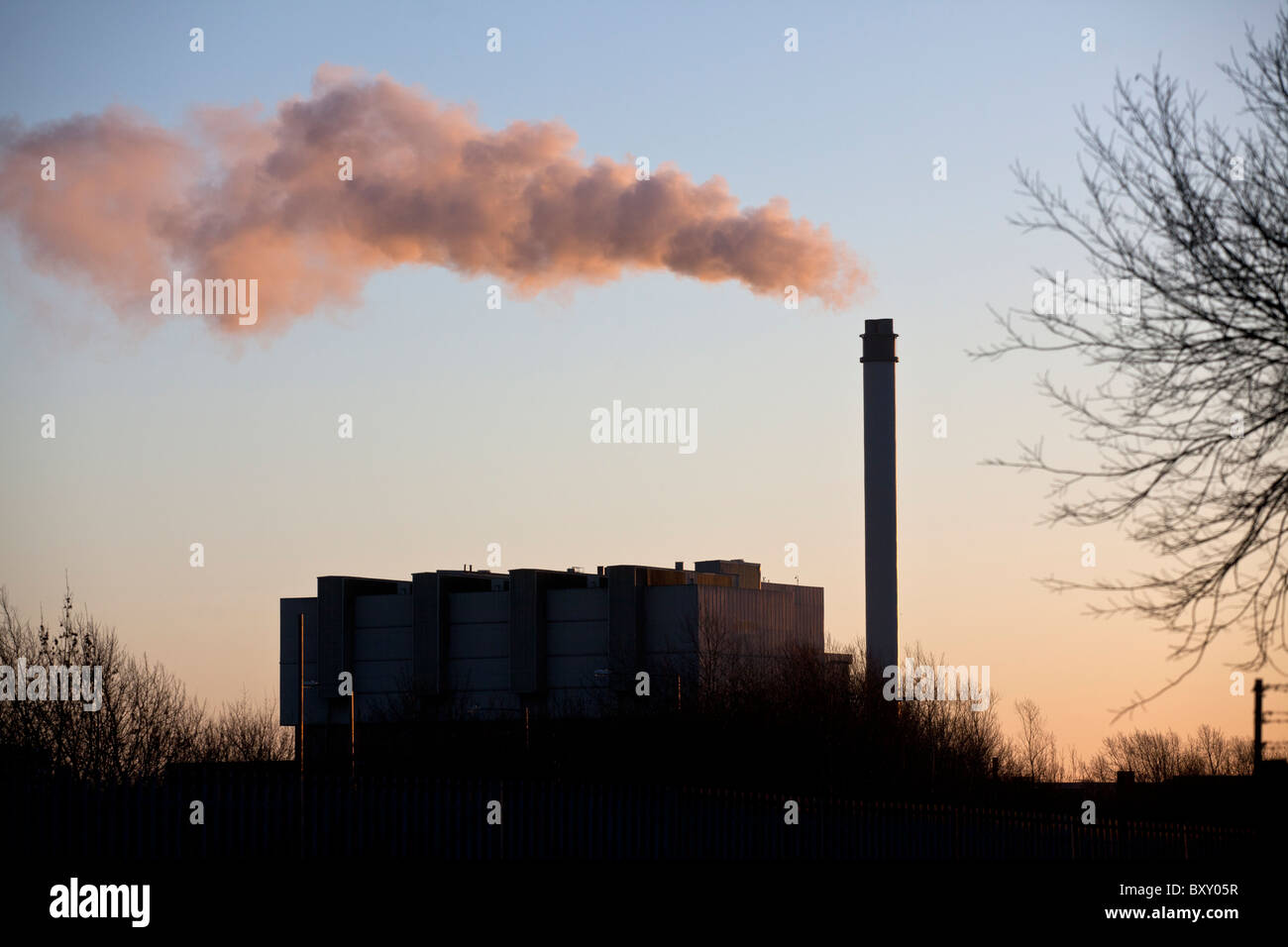 A paper recycling plant belches out steam from it's chimney, Birmingham, UK. - Stock Image