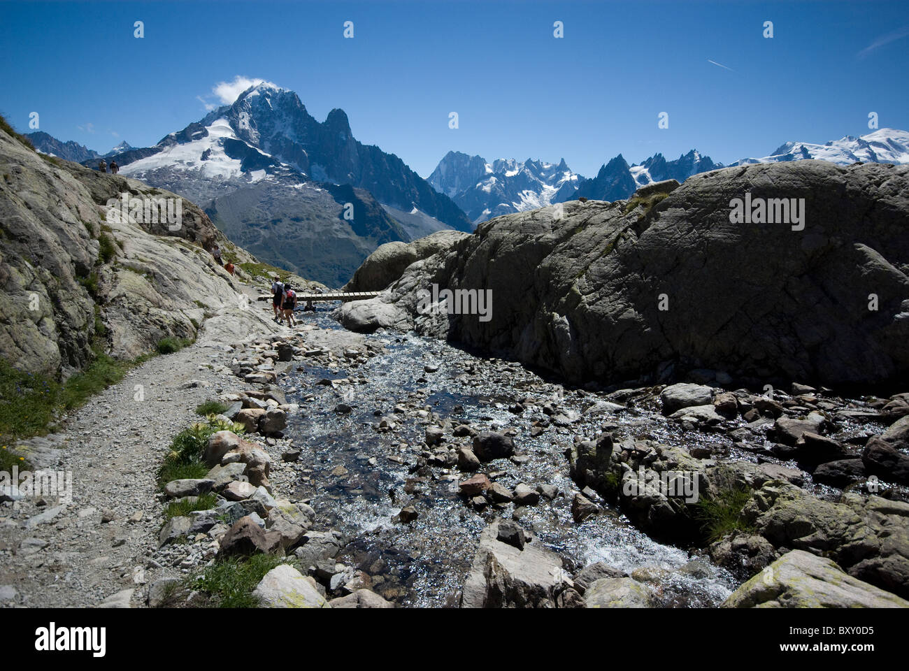 A river leads from Lac Blanc, opposite the peaks of Aiguille Verte and Mont Blanc, French Alps. - Stock Image