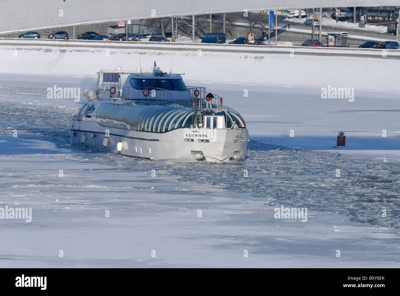 Cruising launch floating on the ice-covered Moscow-river - Stock Image