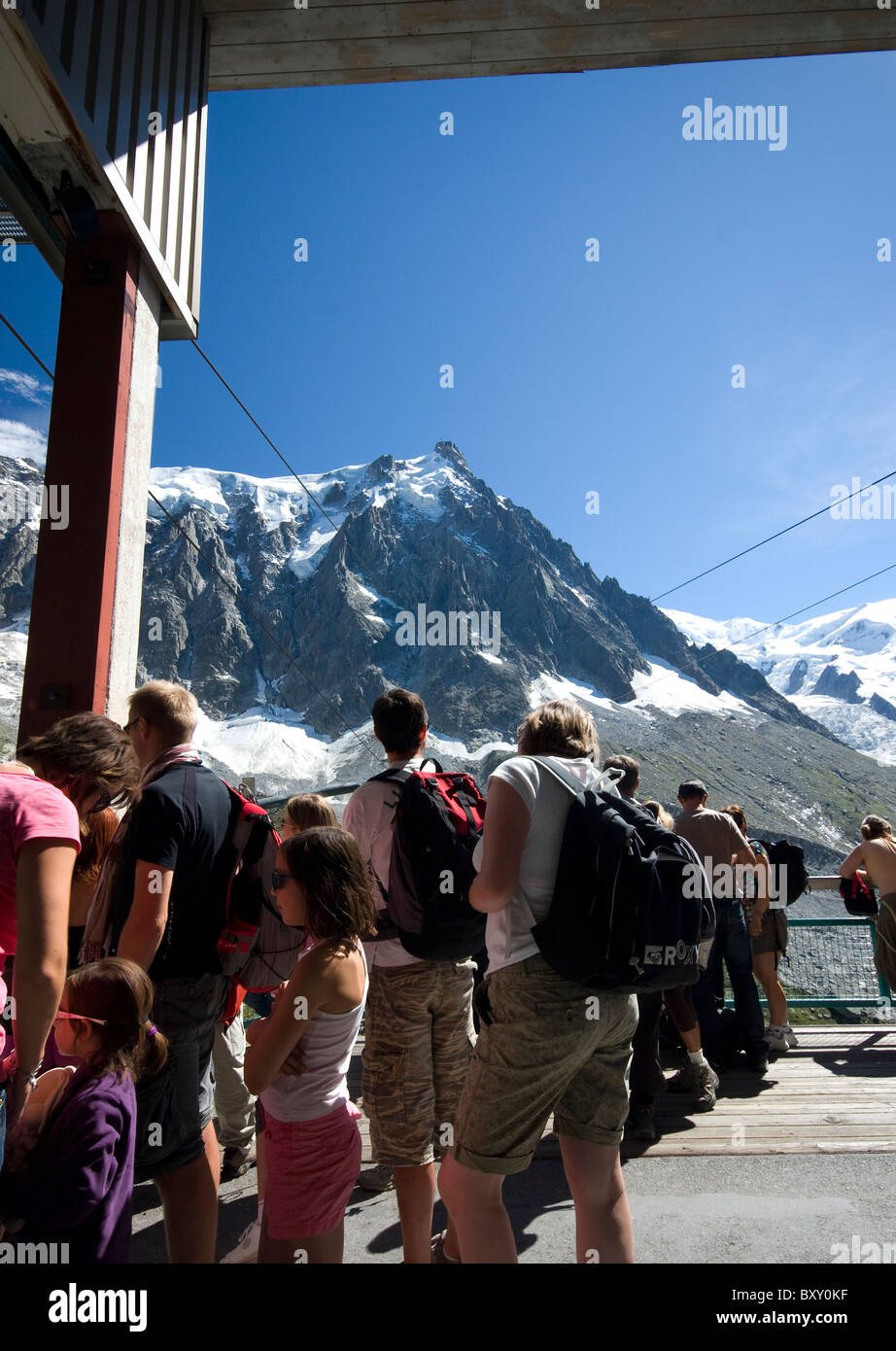 Tourists queue for the cable car to Auguille du Midi - the peak in the distance, Haute Savoie, Alps, France - Stock Image