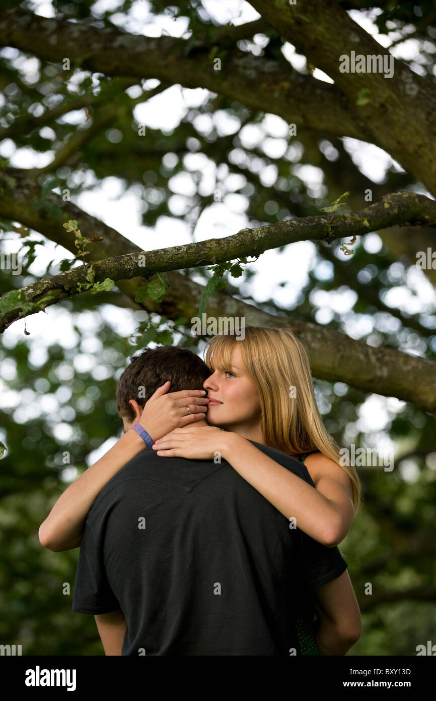 A young couple standing beneath a tree embracing - Stock Image