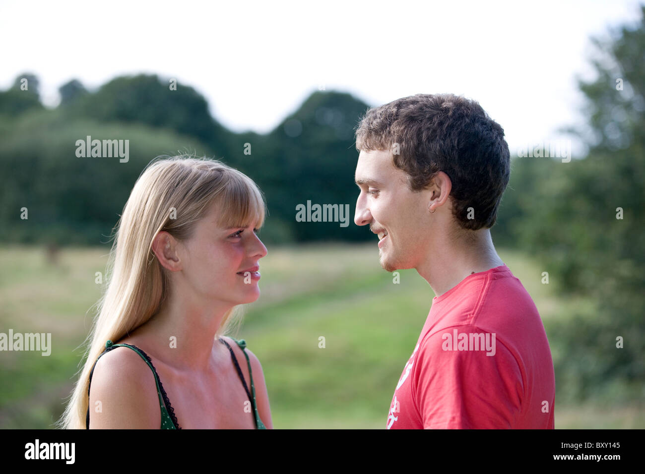 A young couple standing outdoors, smiling at each other - Stock Image