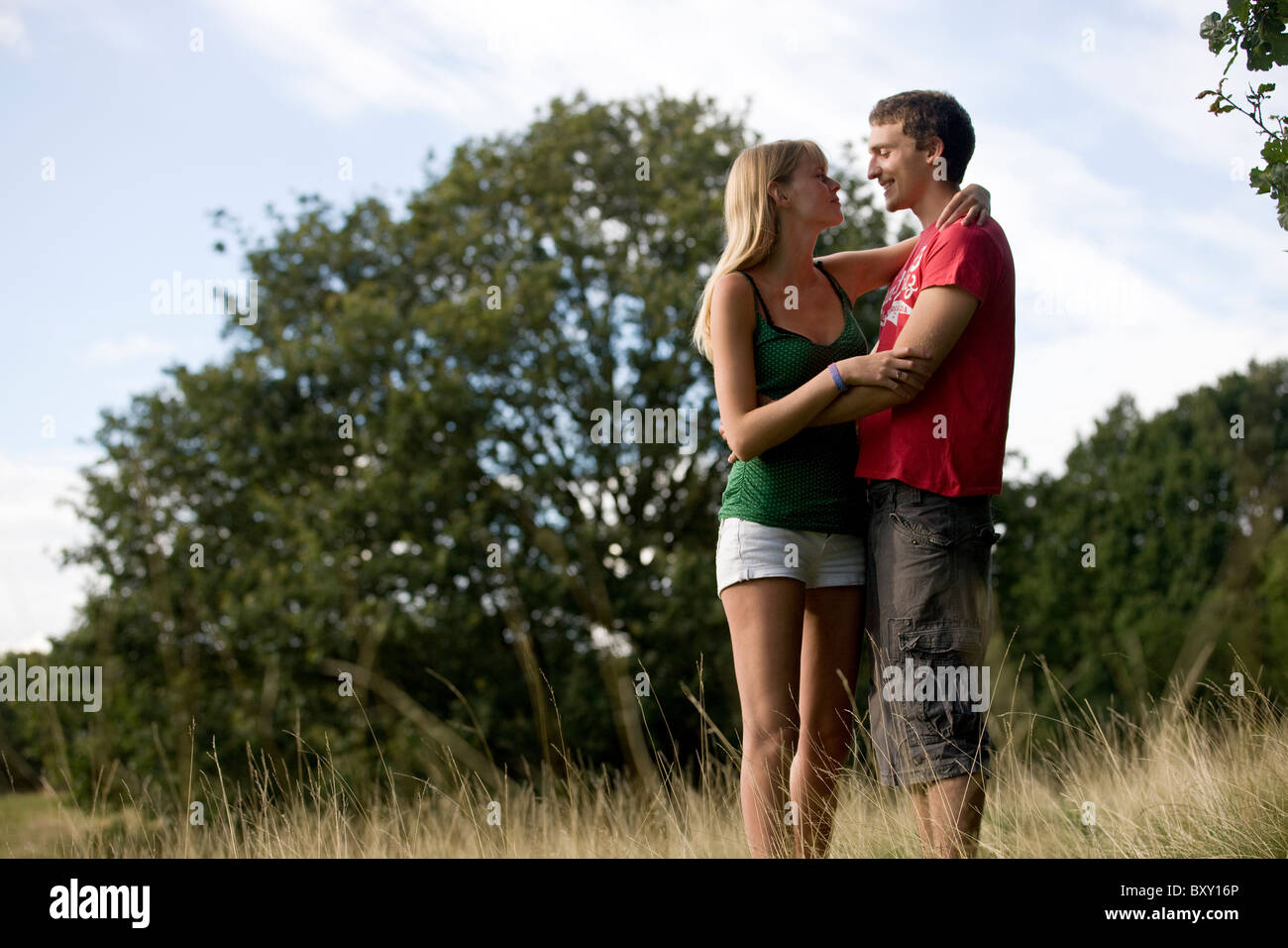 A young couple standing outdoors, embracing - Stock Image