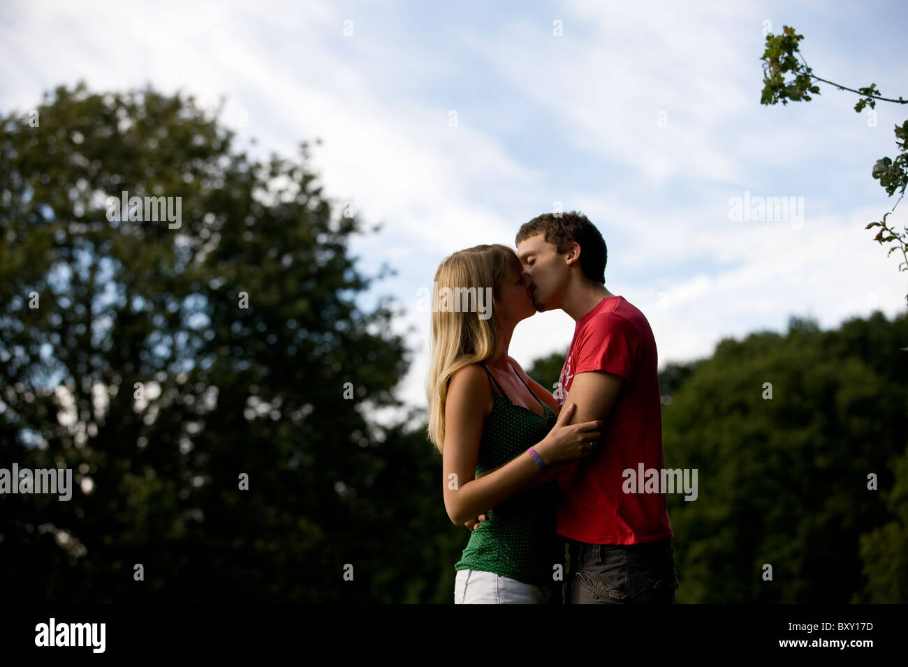 A young couple kissing outdoors - Stock Image