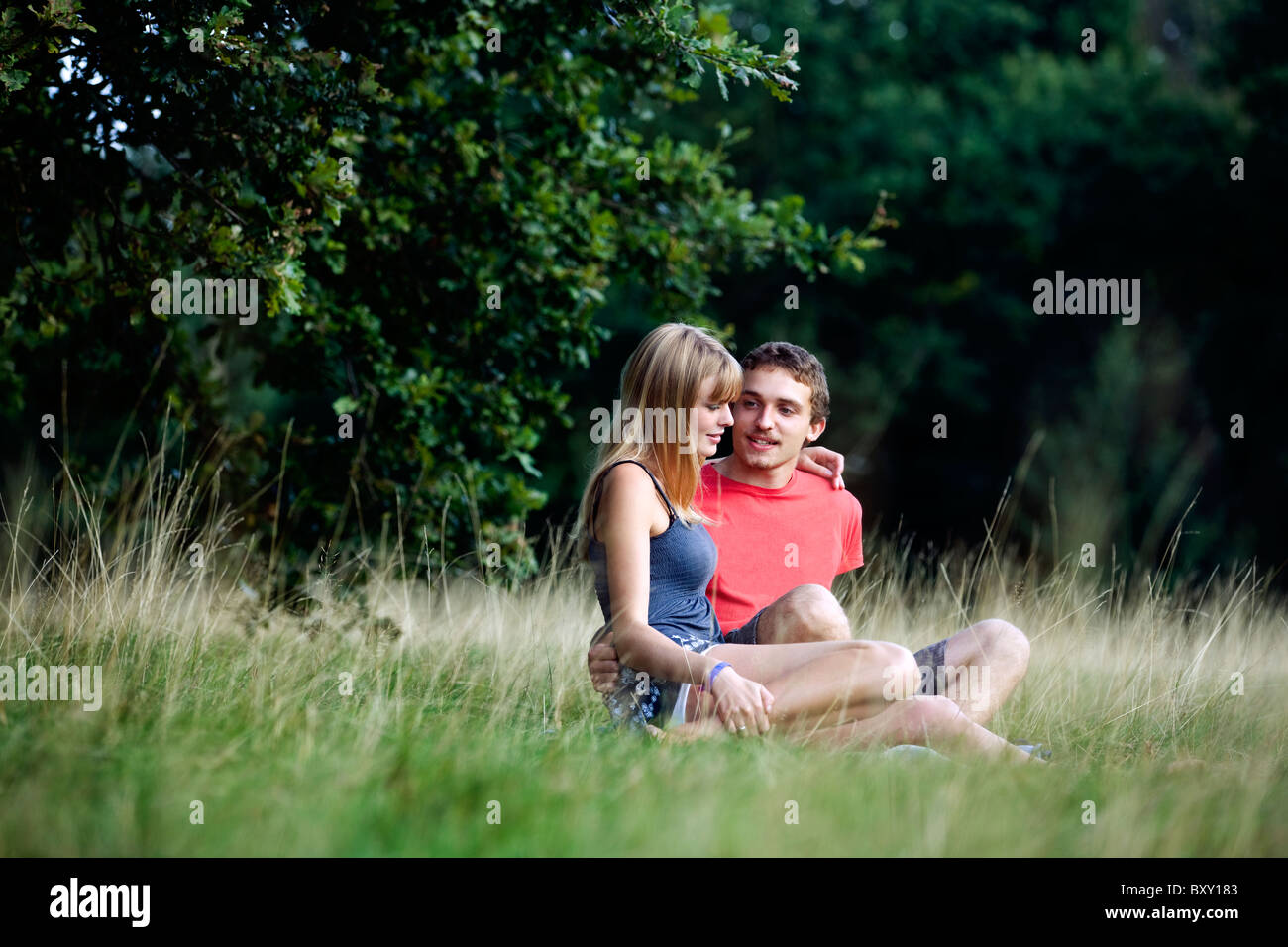A young couple sitting on the grass - Stock Image