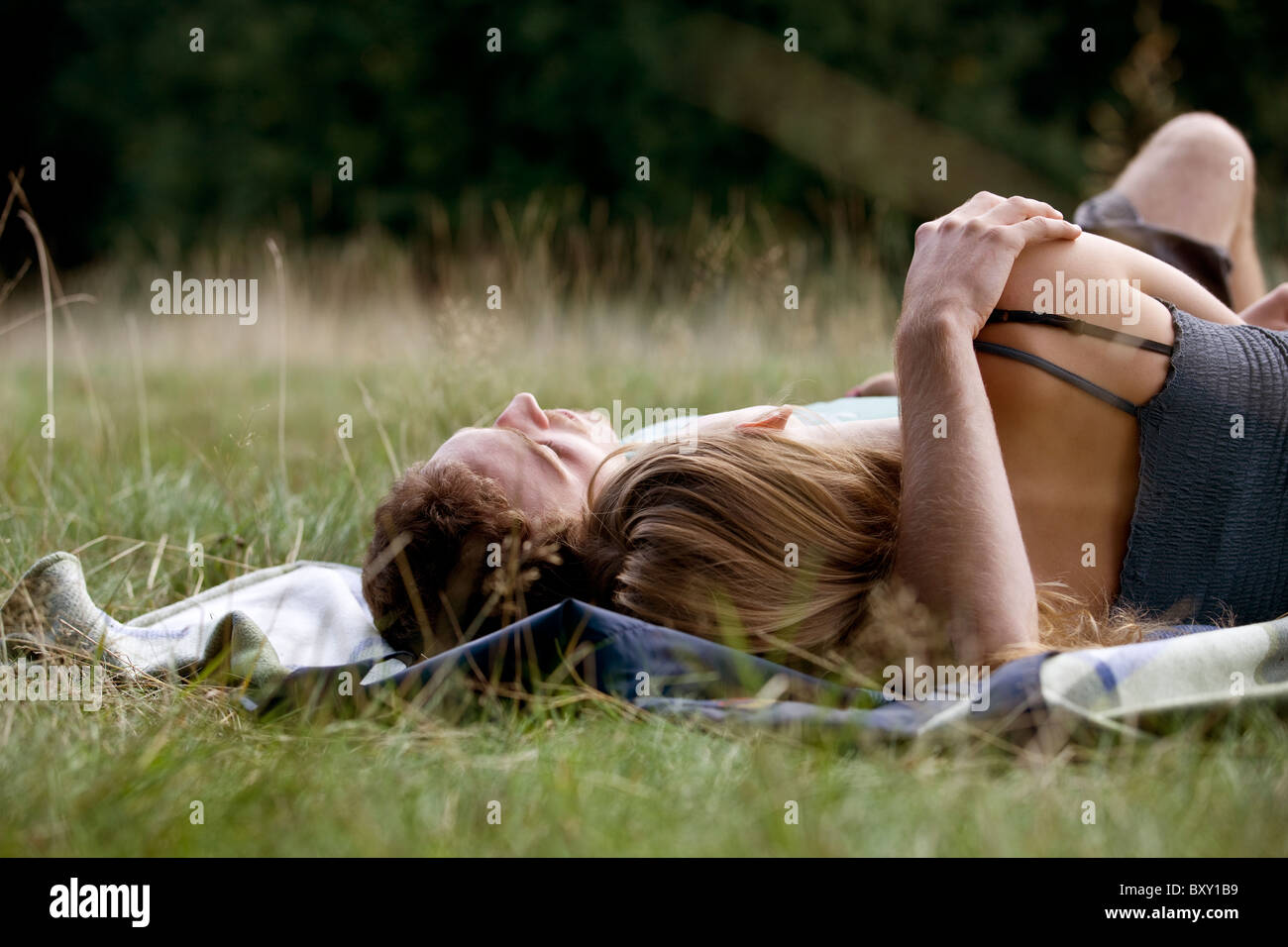 A young couple lying on the grass - Stock Image